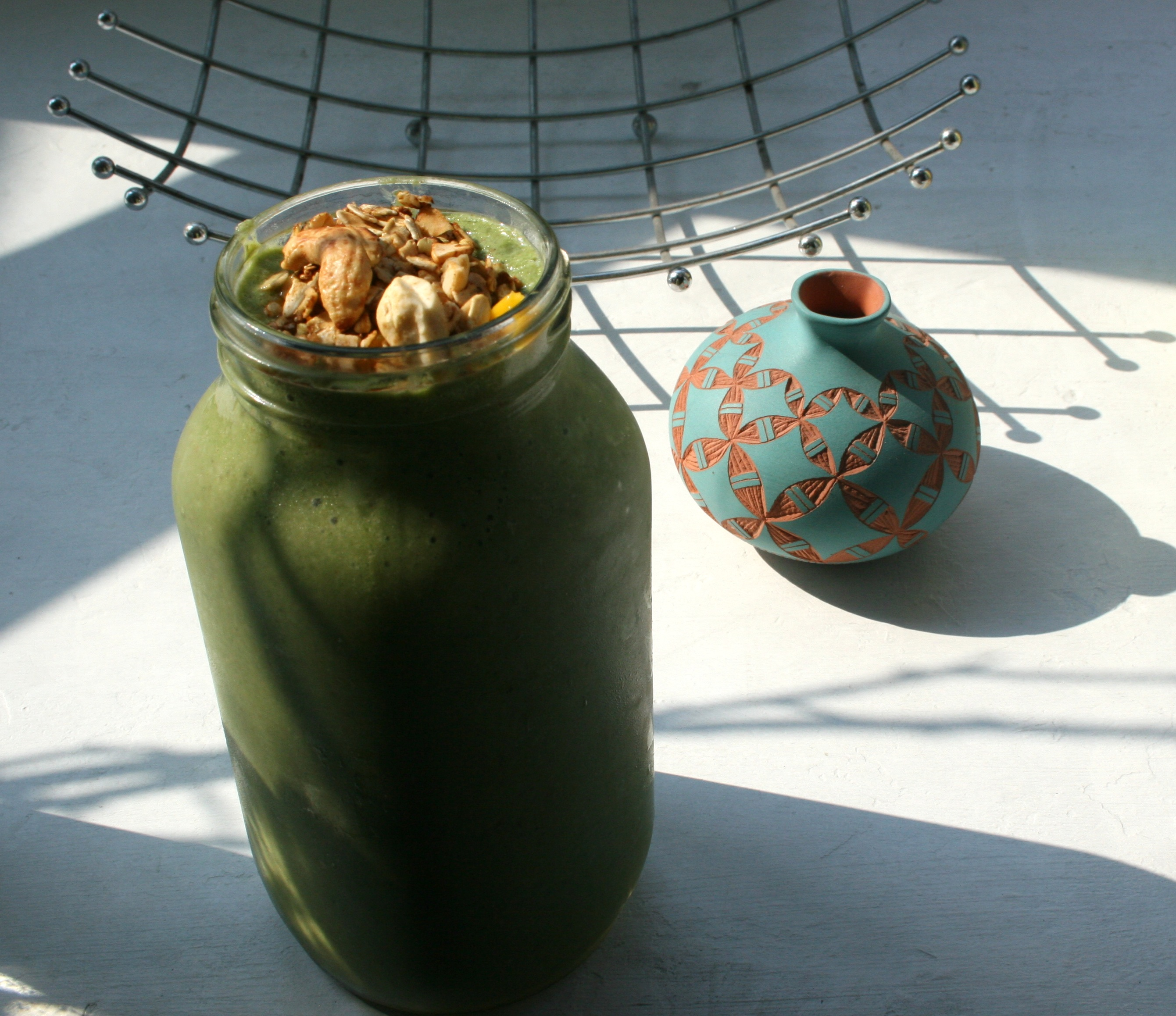Green apple, spinach, cucumber smoothie topped with homemade cashew coconut granola.